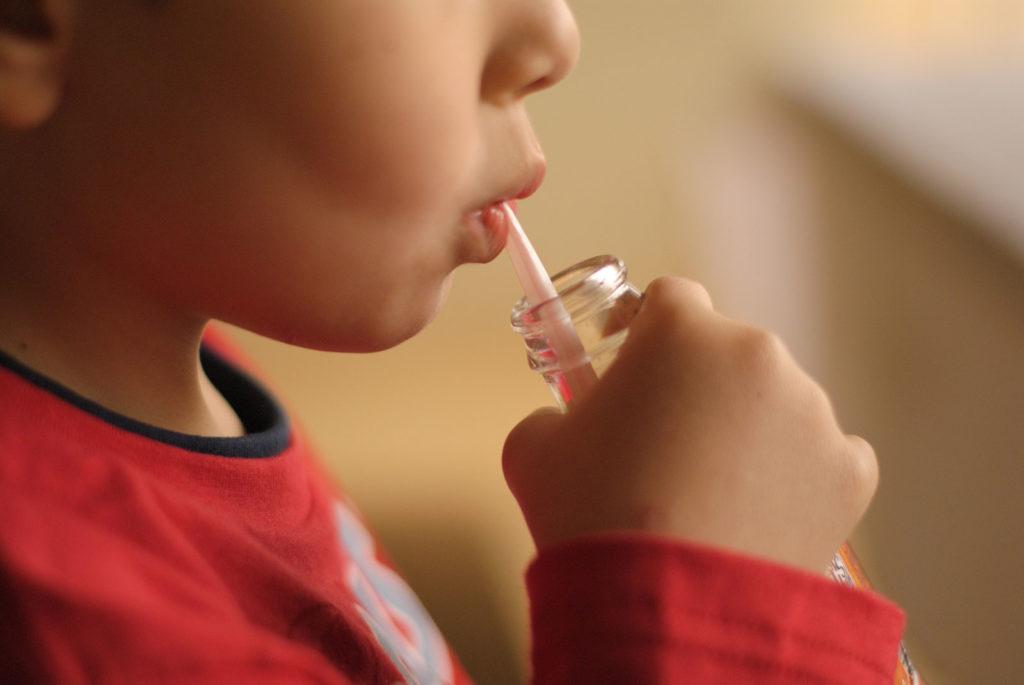 Boy sipping a soda bottle